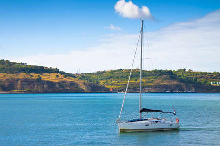 Sailboat with lowered sails is crossing the portuguese Tejo river