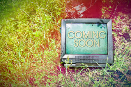newsreader: Old CRT television with Coming Soon written on screen - toned image with copy space