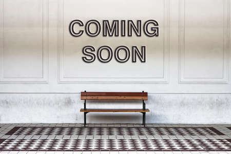 absentee: Coming soon written on a wall above a wooden bench - concept image Stock Photo