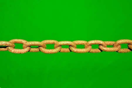 la union hace la fuerza: Old rusty colored chain on green background - toned image Foto de archivo