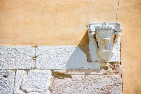 Corinthian capital in stone and plaster wall (Italy)