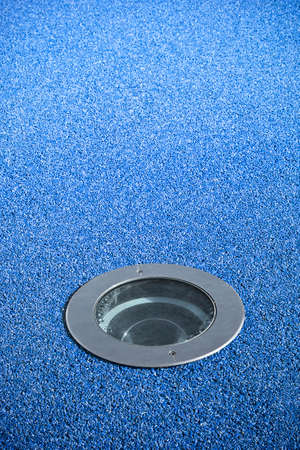 inground: Recessed floor lamp on blue gravel floor - image with copy space Stock Photo