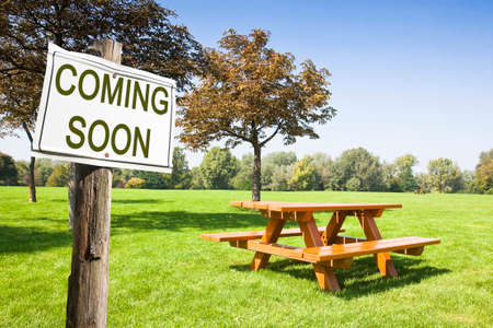 absentee: Coming soon written on a signboard near a picnic table on a green meadow - concept image Stock Photo