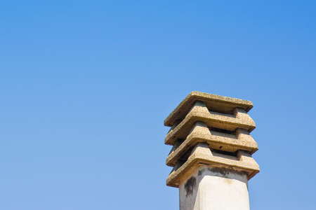 Prefabricated concrete chimney on blue background with copy space