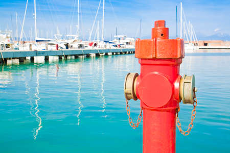 Red hydrant in a italian harbor - concept image with copy space Stock Photo