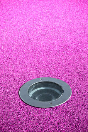 Recessed floor lamp on purple gravel floor - image with copy space