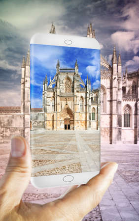 in monastery: Hand holding a smartphone with a picture of Batalha cathedral in Portugal (Europe) - 3D render concept image