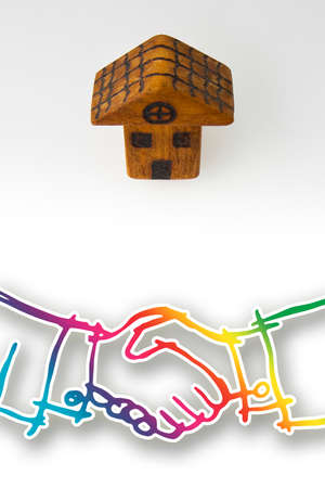 Handshake against a little wooden house - The business of wooden houses concept image