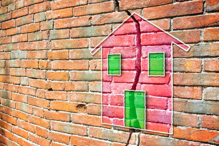 Cracked brick wall with a colored house drawn on it Archivio Fotografico