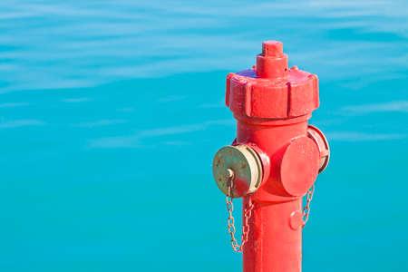 Roter Hydrant gegen einen Wasserhintergrund - Konzeptbild mit Kopienraum Standard-Bild - 89220453