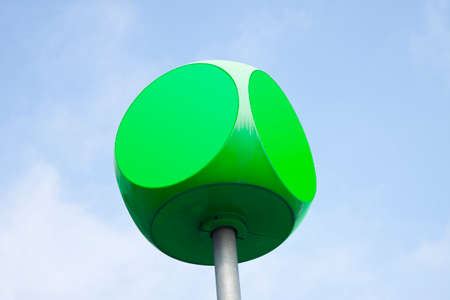 Green  cube with rounded edges against sky background with copy space 版權商用圖片