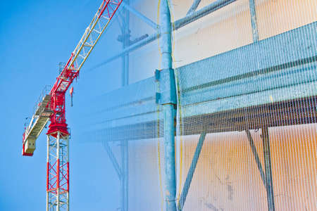 Italian construction site - concept mage with metal scaffolding and tower crane