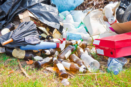 Illegal dumping with bottles, boxes and plastic bags abandoned in nature Foto de archivo