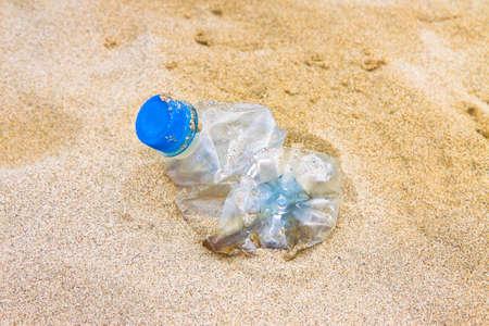 해변에 버려진 물의 빈 구겨진 된 플라스틱 병 스톡 콘텐츠