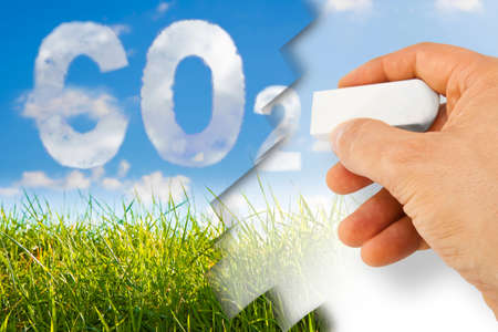 Hand removes CO2 - concept image against a green wild grass on sky background