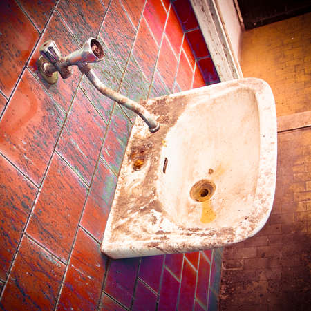 Old sink in a public abandoned restroom - toned image Stock Photo