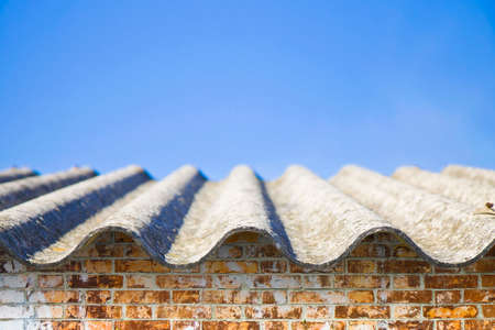 Asbestos roof above an old brick wall - image with copy space