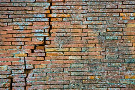 Cracked brick wall. Deep crack in a brick wall