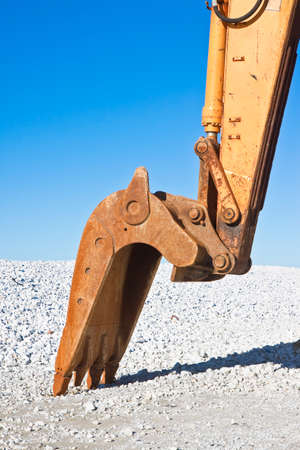 Detail of excavators bucket at a gravel seaside Stock Photo