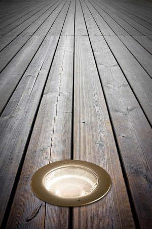Recessed floor lamp on old wooden floor - image with copy space Standard-Bild