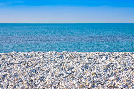Expanse of white gravel on the sea coast with calm sea on background Imagens
