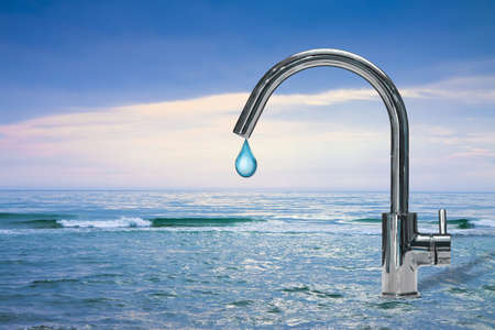 An improbable faucet at the seaside is pouring a drop of water - Plenty of water concept image
