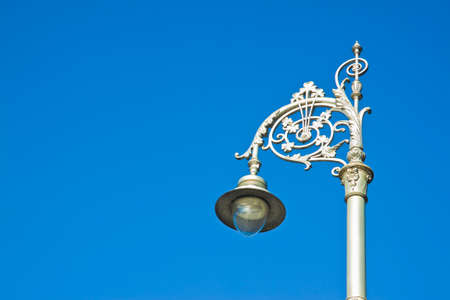 Typical classic Irish streetlight against a blue background - image with copy space