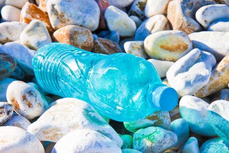 Empty green plastic bottle abandoned on gravel beach Stock Photo