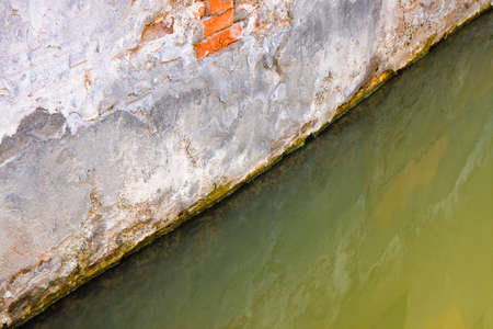 Rising damp on a brick wall in a channel full of water Stock Photo