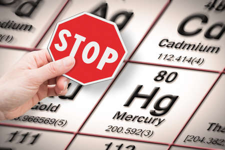 Stop heavy metals - Concept image with hand holding a stop sign against a mercury chemical element with the Mendeleev periodic table on background Banque d'images