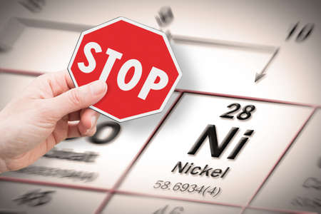 Stop heavy metals - Concept image with hand holding a stop sign against a Nickel chemical element with the Mendeleev periodic table on background