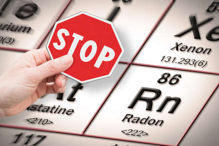 Stop heavy metals - Concept image with hand holding a stop sign against a radon chemical element with the Mendeleev periodic table on background Stock Photo