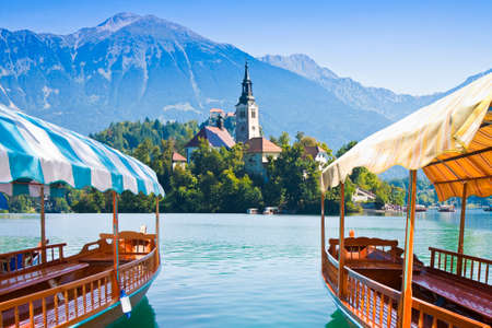 """Typische houten boten, in Sloveens noemen """"Pletna"""", in het meer van Bled, het beroemdste meer in Slovenië met het eiland van de kerk (Europa - Slovenië) Stockfoto"""
