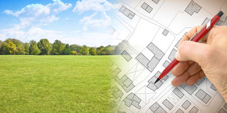 Een nieuwe stad plannen - conceptafbeelding met hand tekenen van een denkbeeldige kadastrale kaart van grondgebied met gebouwen, velden en wegen tegen een groen gebied
