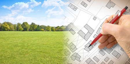 Planen einer neuen Stadt - Konzeptbild mit der Hand, die eine imaginäre Katasterkarte des Territoriums mit Gebäuden, Feldern und Straßen gegen eine Grünfläche zeichnet