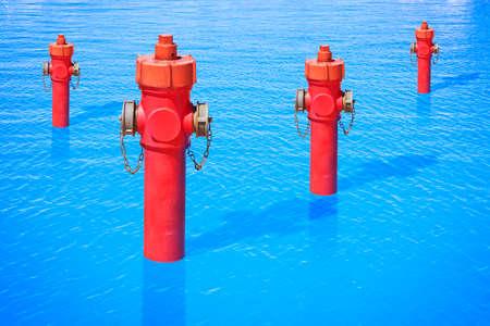 An improbable hydrant in the ocean. Plenty of water: concept image Stock Photo