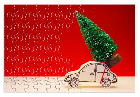 Hurry up! Christmas is coming! Holiday concept with a small pine tree on handmade cartoon toy car in jigsaw puzzle shape Stock Photo