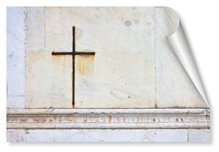 Iron Christian cross snuggled against a white stone on a italian facade church - curl and shadow design concept image with copy space Standard-Bild