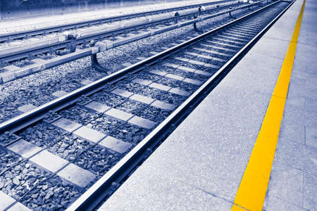 Detail of a metal European railway with sidewalk and yellow safety dividing line - toned image with copy space Stock fotó