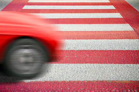 Red and white pedestrian crossing with car on foreground. Notes for the Ispector: the silhouette of the car has been modified and is not recognizable Stock Photo