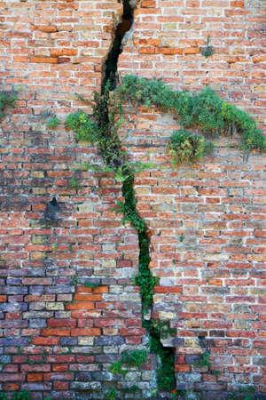 Cracked brick wall - Deep crack in a brick wall Stock Photo