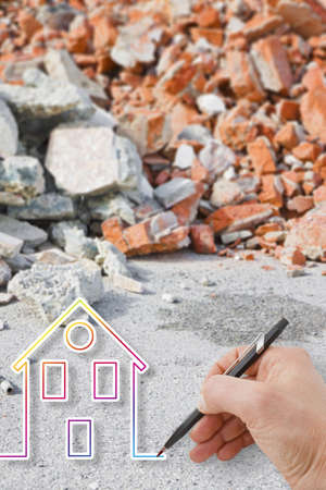 Hand drawing a colored house against a concrete and brick rubble debris - earthquake reconstruction concept image