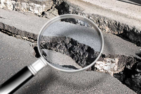 Cracked asphalt road damaged after a structural failure - Concept image seen through a magnifying glass Imagens