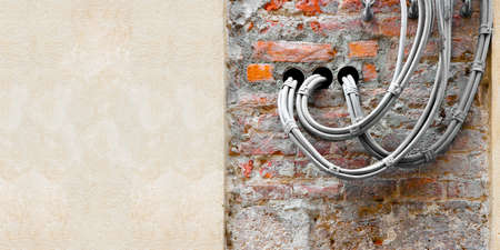 Electrical power and telephone cables against a brick and plaster wall - image with copy space