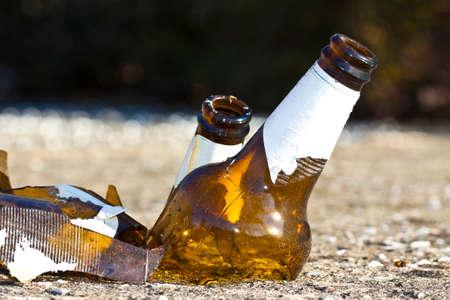 Shattered beer bottle resting on the ground: alcoholism concept