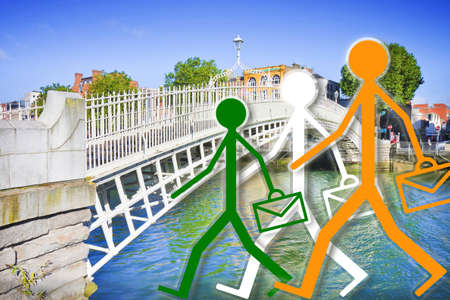 Coming to work in Ireland - concept image with the famous Half penny bridge in Dublin and employees on foreground 写真素材