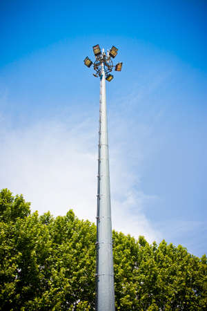 Outdoor train station lights and telecommunication tower against blue sky. Circle of bulbs, cell phone gsm antennas on tall metal pole.