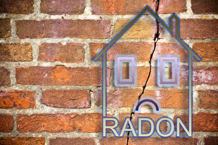 The danger of radon gas in our homes - concept image with an outline of a small house with radon text against a cracked brick wall