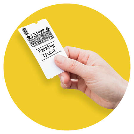 Female hand holds a parking ticket - parking payment concept - Round icon concept image - Photography in a yellow circle