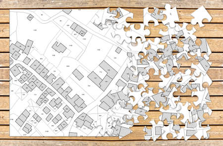 Imaginary cadastral map of territory with buildings and roads - concept image in jigsaw puzzle shape on wooden background